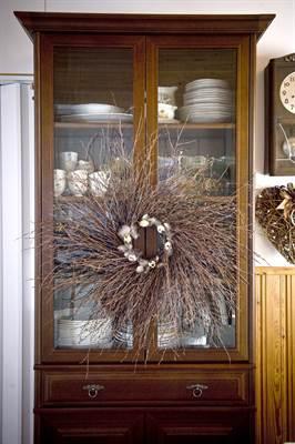 Sisällä sesonkiin sopivat kranssit voivat kaunistaa kotia vaikkapa vitriinien ovissa.